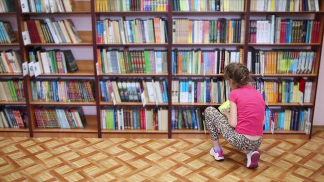 Woman kneeling before book shelves